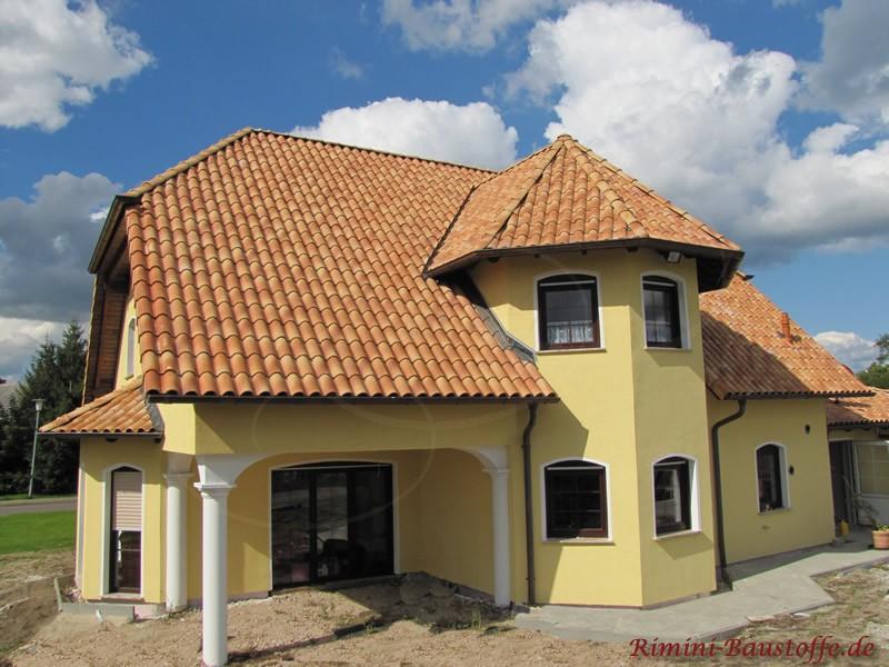 Großes Haus mit Krüppelwalmdach in südlichen Farben. Es ist ein kleiner Erker und ein Turm mit Runddach zu sehen