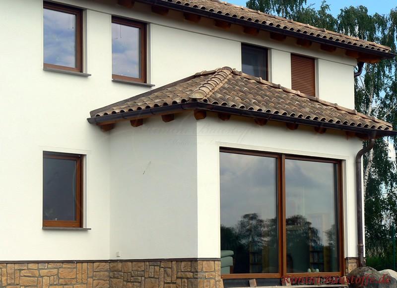 Weiße Fassade und braunes Dach im rustikalem Charakter. Das Haus hat einen Sockel aus Riemchen