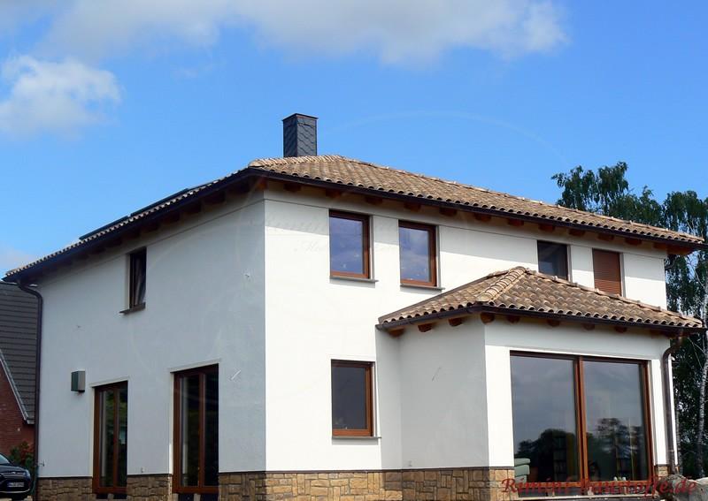 Stadtvilla mit schönen Dachziegeln und Natursteinsockel. Die Fenster sind wie die Ziegel und der Sockel bräunlich