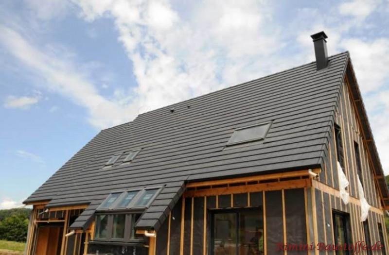 Großes Satteldach mit Glattziegeln in schwarz. Die Fassade ist noch im Holzständerwerk.