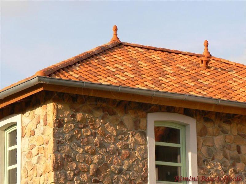 Felsenfassade mit grünen Fenstern und schönen Dachziegeln