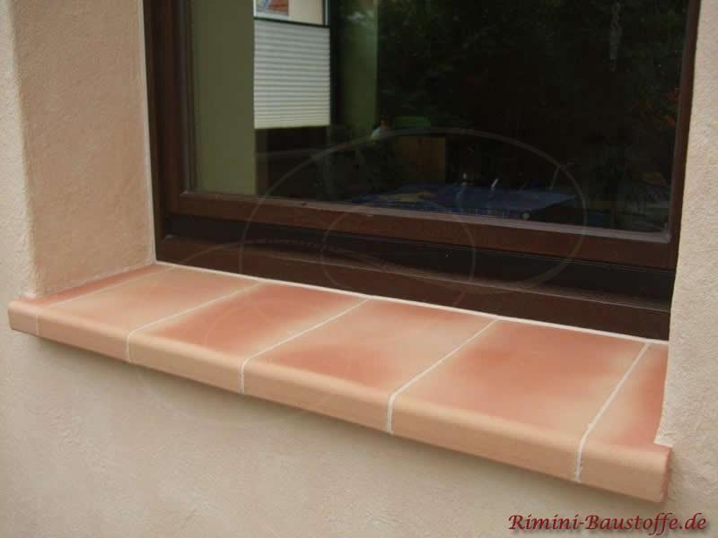 Putzfassade und braune Fensterrahmen mit passenden Fensterbaenken