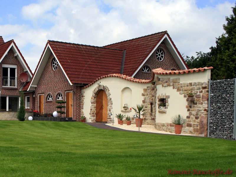 Sehr schöne Gartenmauer mit Riemchen, beigen Putz, Pflanzen und mediterraner Mauerabdeckung