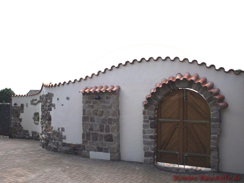 Weiße Putzmauer mit großer Holztür, Natursteinelementen und Mauerabdeckung aus Dachziegeln