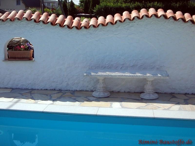 Weisse Gartenmauer mit Fenster vor einem Swimmingpool. Als Mauerabdeckung kommen Dachziegel zum Einsatz.