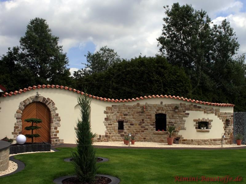 Geschwungene Putzmauer mit Natursteinen und Dachziegeln verziert