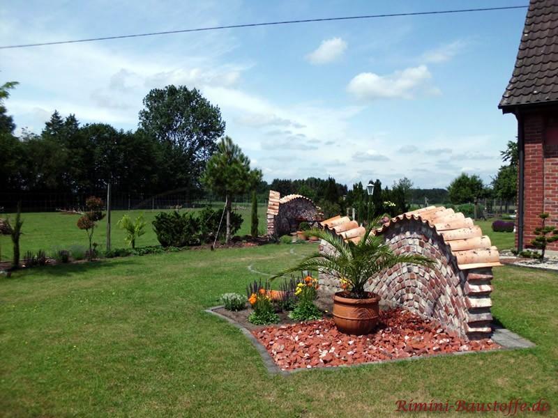 Weitläufiger Garten im Sommer. Eine kleine Mauer im individuellem Design im Vordergrund