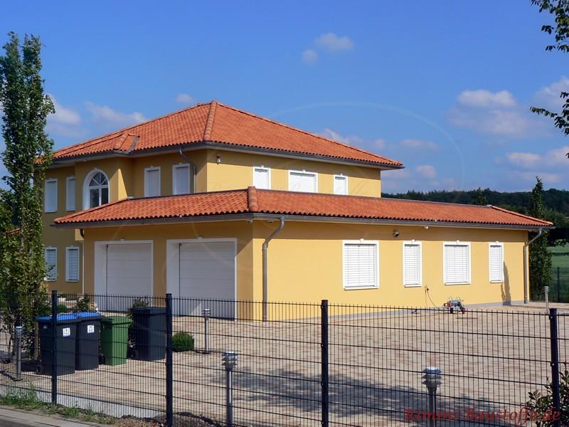 Stadthaus mit gelblicher Fassade und rot geschecktem Dach
