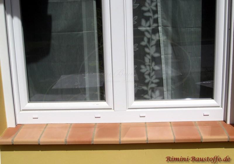 lachsfarbene Fensterbank zu weissen Fensterrahmen und gelber Putzfassade
