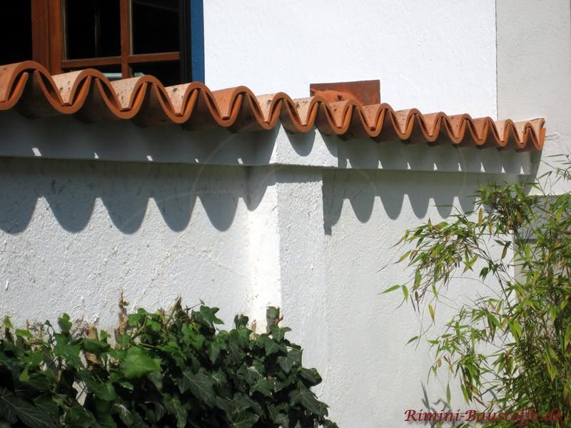 Weiße Putzmauer mit sehr gering geneigten Dachziegeln abgedeckt. Nahaufnahme