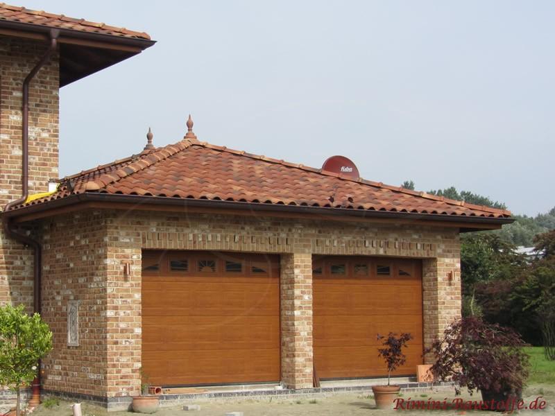 Doppelgarage mit schönen Holzfarbenen Toren und Zierspitzen auf dem Dach