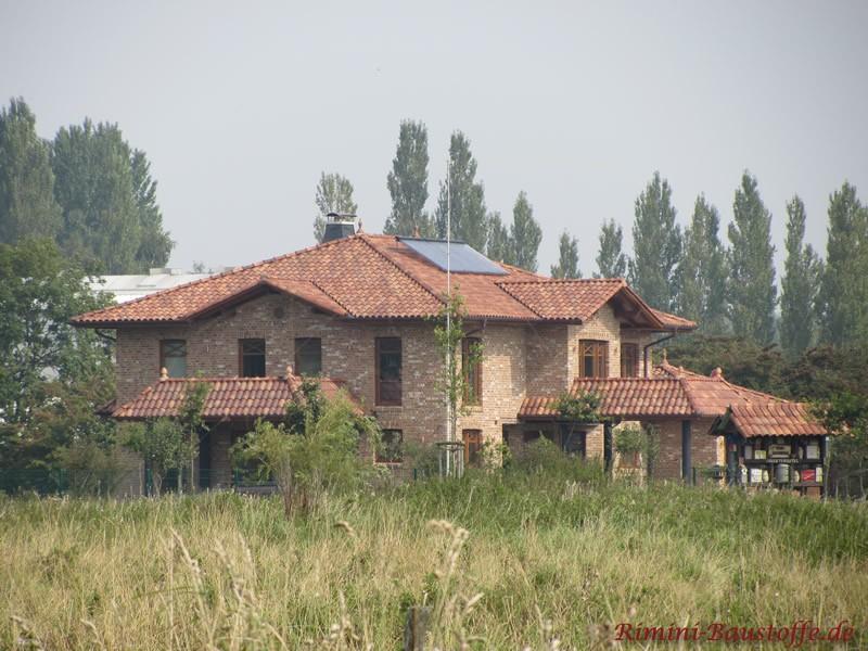 mediterranes Wohnhaus im Grünen mit heller Klinkerfassade und schönem passenden Dach