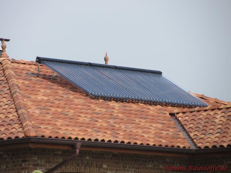 Solaranlage auf einem mediterranen Dach. Schöner Dachschmuck durch Zierspitzen