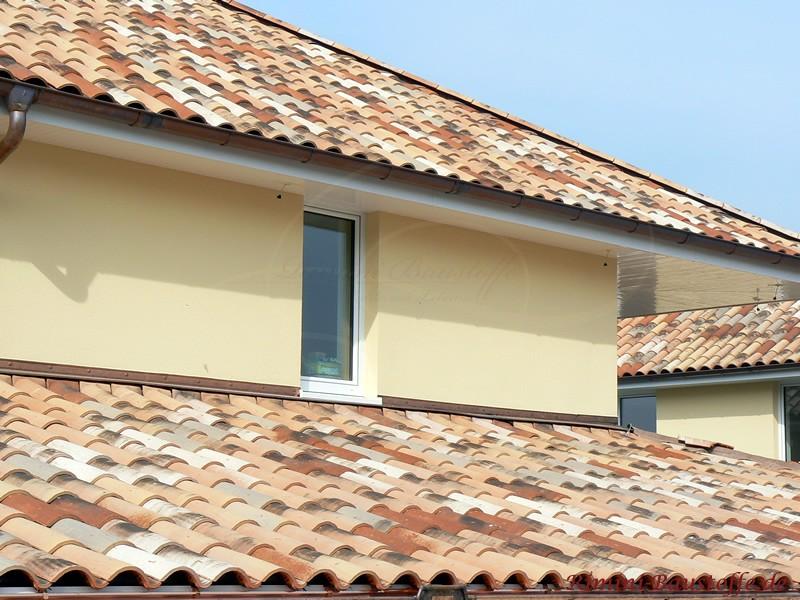 mehrgeschossiges Dach mit schöner heller Putzfassade und einer Dachziegelfarbe in Herbstlaubmischung