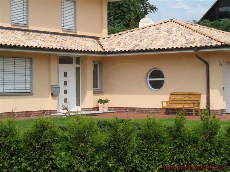 Beiger Putzbau mit rundem Fenster und hellen Dachziegeln