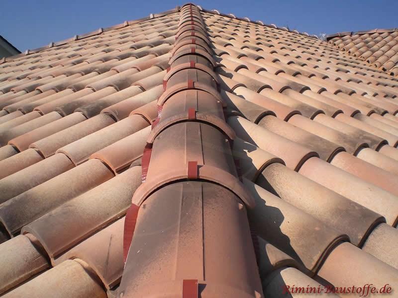 Auf dem Bild ist ein sehr gewölbter Dachziegel zu sehen in den Farben beige, rot und schwarz. Auch ein Halbrunder Walm ist zu sehen