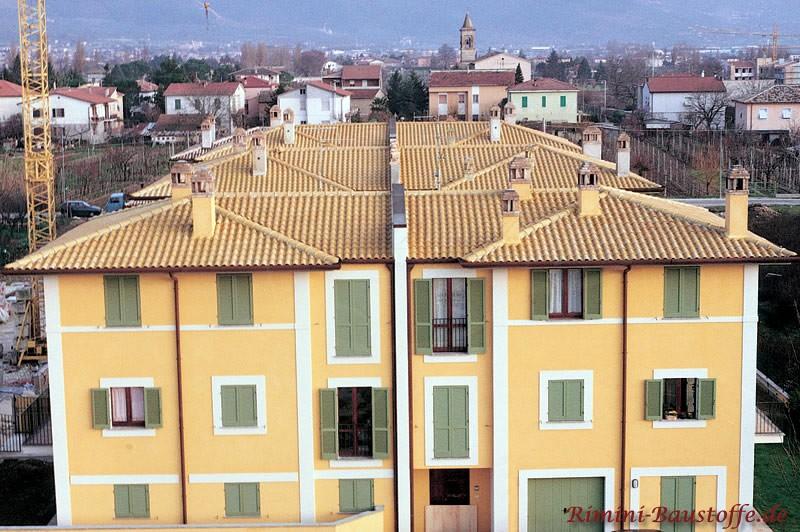 Großes Mehrfamilienhaus mit gelben Putz, gelben Dach und hellgrünenfarbenen Fensterläden