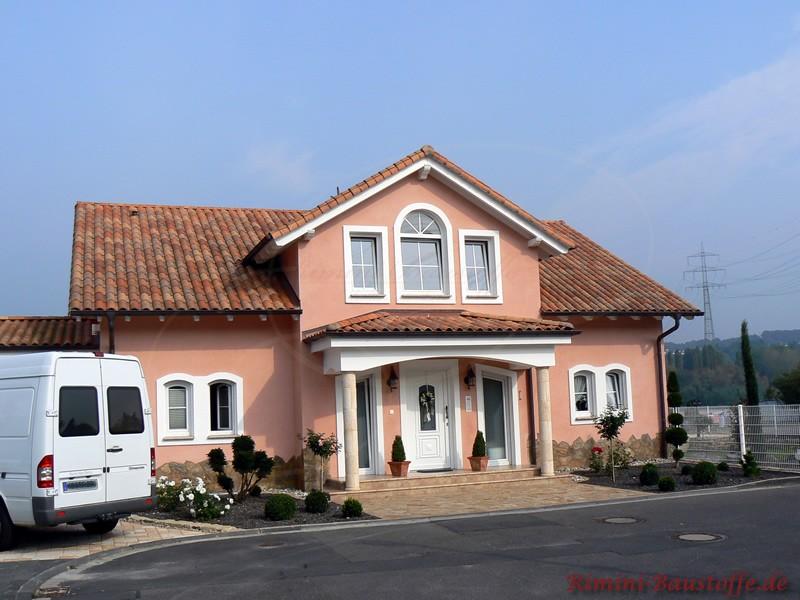 Massivhaus mit buntem Dach und weißen Fenstern