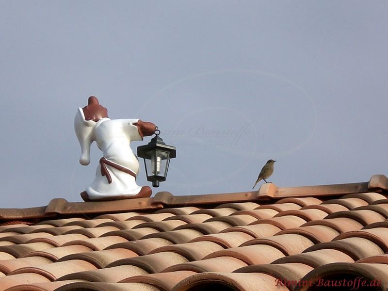 Schlafwandelndes Männchen auf einem First als Dachschmuck. Die Dachziegel sind stark gewölbt und mehrfarbig