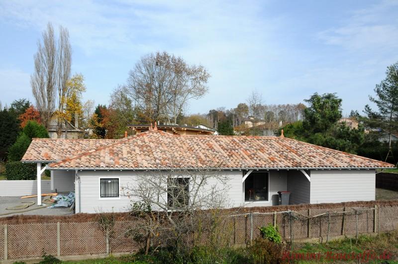 weiße Holzfassade mit schönem passenden Dach in hellen Rottönen
