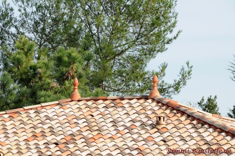 zwei Zierspitzen auf einem Walmdach mit mediterranen Ziegeln
