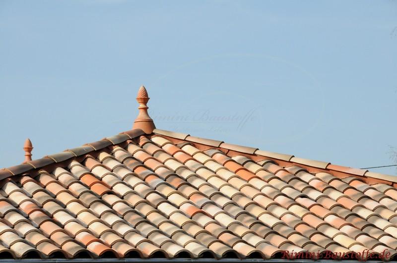 zwei Zierspitzen als Dachschmuck auf einem Dach mit mediterranen Ziegeln