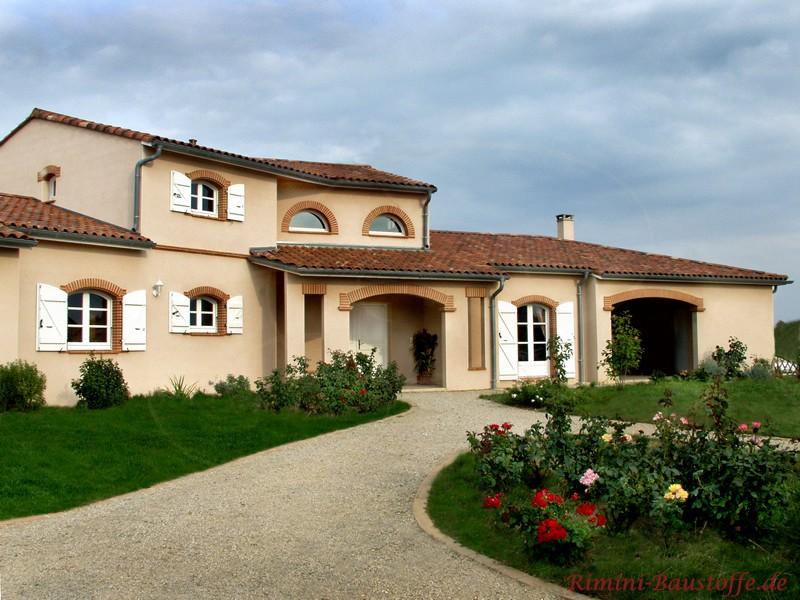 schöne große Villa im mediterranen Stil mit sandfarbener Putzfassade und einem kräftigen fast braunem Dach