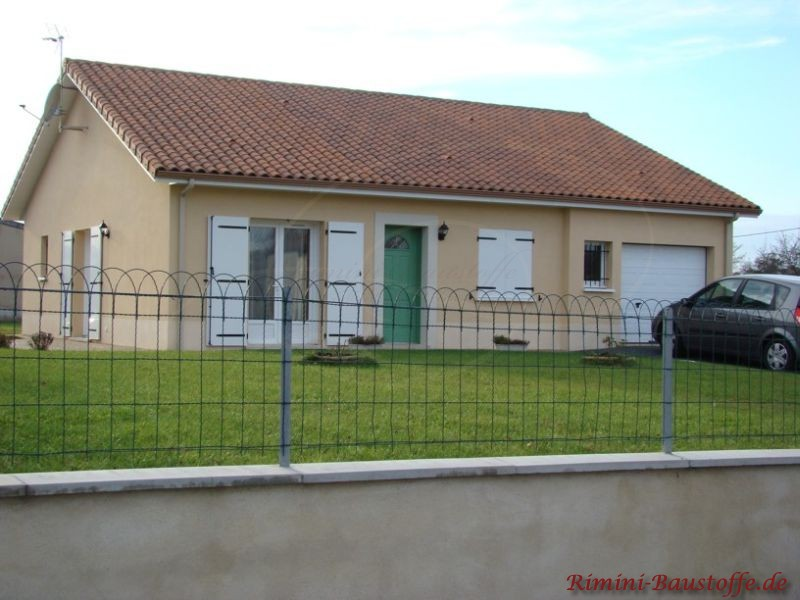 Kleines Einfamilienhaus mit braunem Dach und weißen Fensterläden