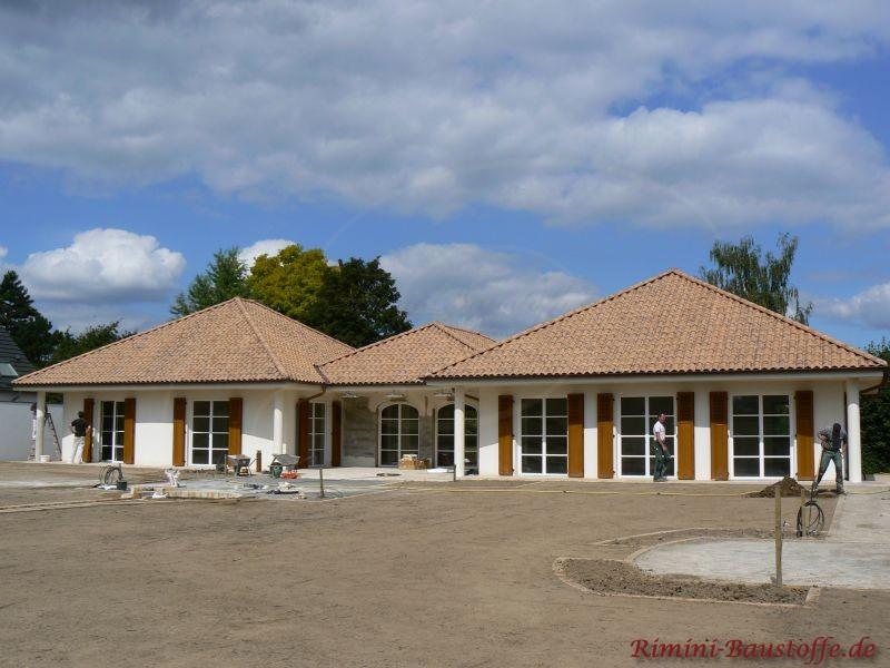 Walmdachbungalow mit braunem Dach und braunen Holzfensterläden