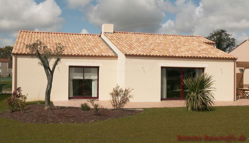 Kleines Putzhaus mit dunklen Fenstern und hellem Dach