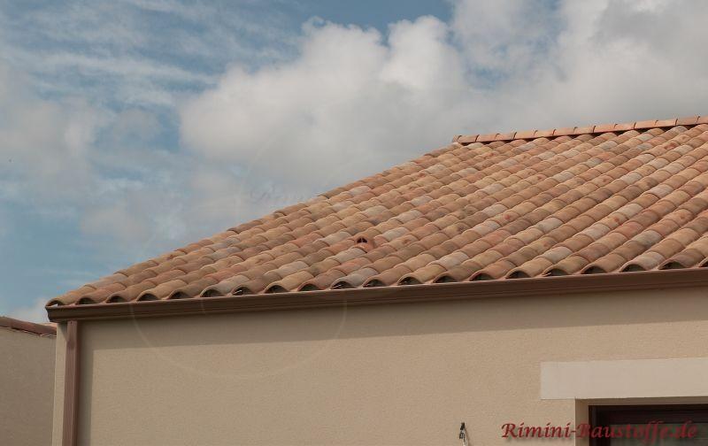 Helles Haus mit gescheckten Dachziegeln und Fenstersturz