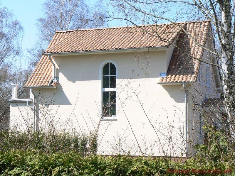 Kleines Einfamilienhaus mit hellem Putz und braunen Ziegeln