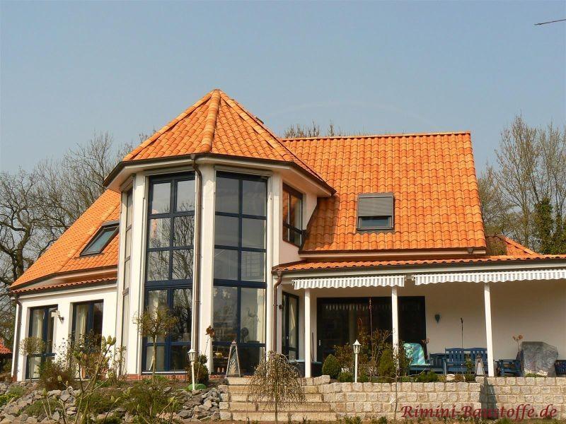 Haus mit grosszügigem Wintergarten in runder Form und organgfarbenem Dach