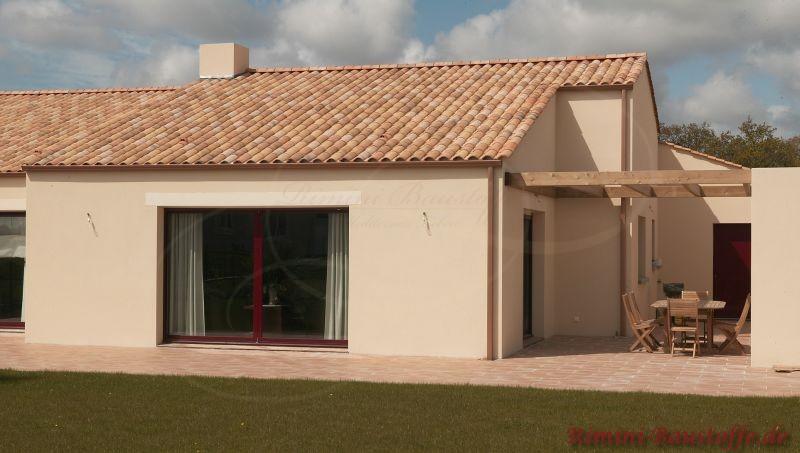 Kleines Haus mit bunt engobiertem Dach und beiger Fassade. Es ist auch ein Panoramafenster zu sehen