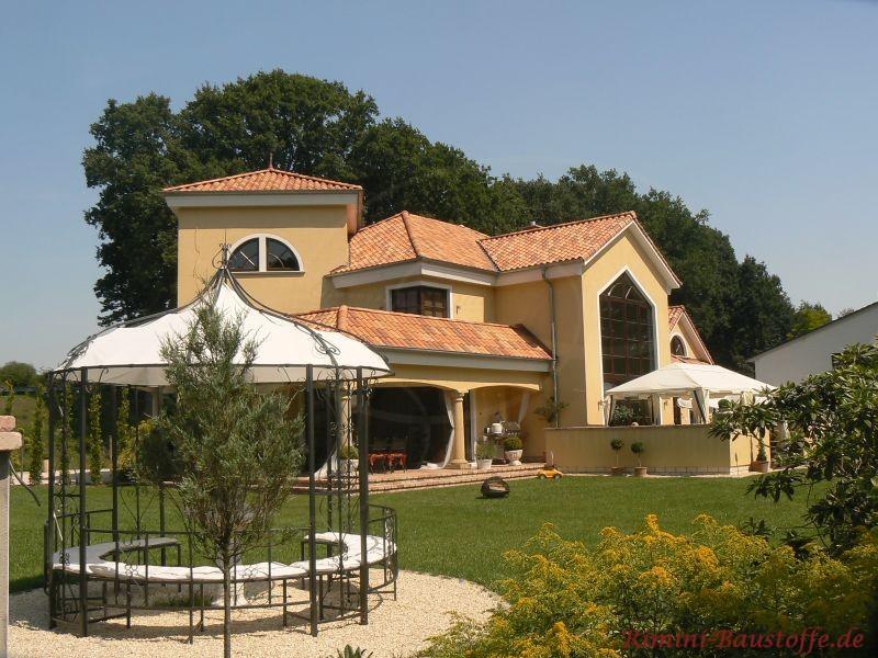 Großzügiges Haus mit gelber Fassade und buntem Dach