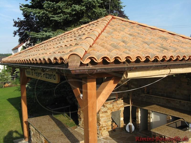 Kleines Spitzdach das auf einer Eichenbalkenkonstruktion ruht. Darunter befindet sich ein italienischer Pizzaofen