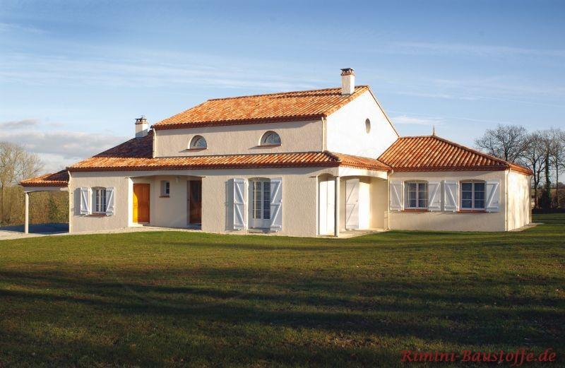 Landhaus mit mediterranem Flair. Buntes Dach, helle Fassade und Fensterläden
