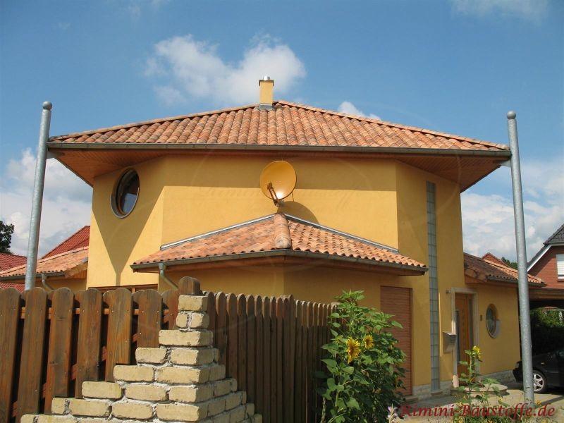 Gelbliches Haus mit Erker und buntem Dach