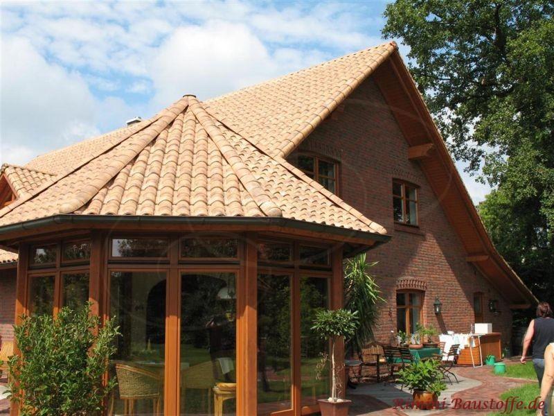 Anbau eines Wintergartens mit rundem Dach und dunklen Fenstern