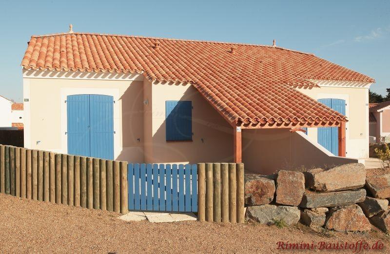Blaue Fensterläden mit buntes Dach und helle Fassade