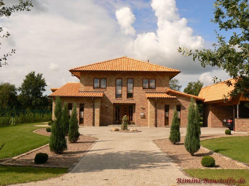 Mediterranes Haus mit Klinkerfassade und langer schöner Hofeinfahrt
