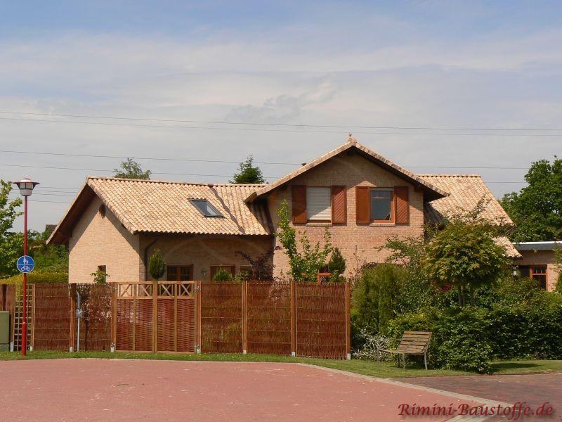 Steinfassade mit bunten Dachziegeln und braunen Fenstern