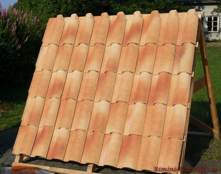 Stohfarbene Dachziegel auf einem Holzständer.
