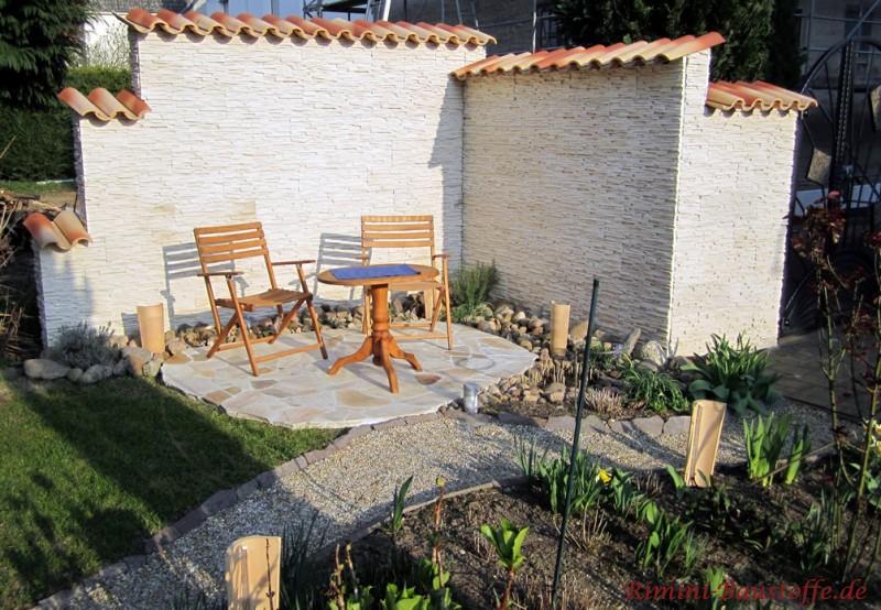 gemütliche Gartenecke mit einer Mauer in feiner heller Schieferoptik