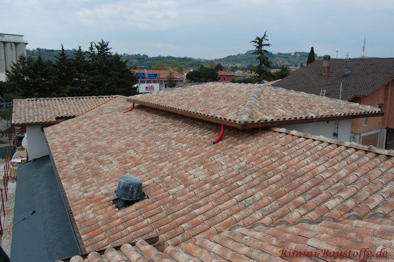 Rustikale Dachlandschaft in rot, schwarz und weißen Farben.