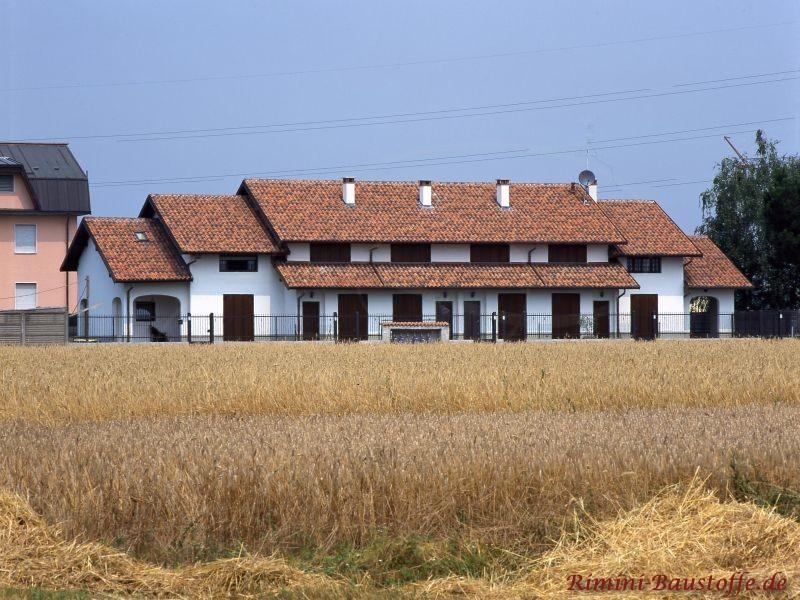 Riesiges Mehrfamilienhaus in Italien aufgenommen aus der Ferne. Es ist ein goldenes Getreidefeld im Vordergrund zu sehen.