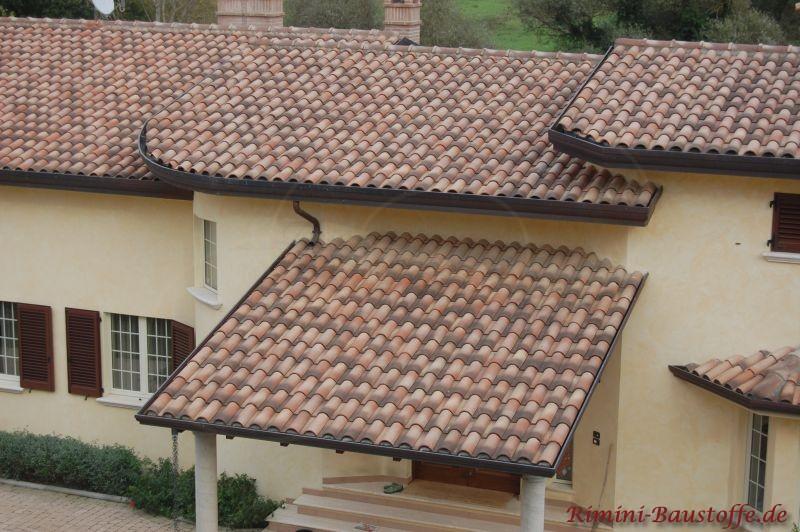 Haus mit wild geschecktem Dach und gelber Fassade. Hier wurden auch braune Fensterläden eingesetzt