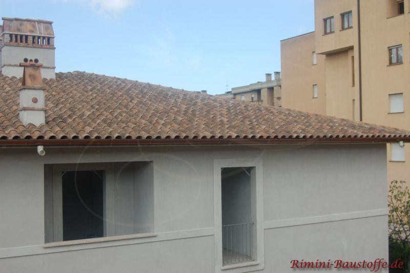 Rohbau eines Hauses, dass eine helle Fassade erhält und rustikale Dachziegel in verschiedenen Engoben