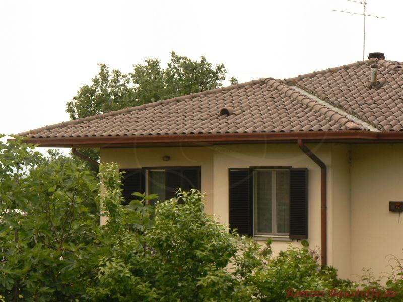 Flachgeneigtes Dach im Norden Italiens. Die Fassade ist geputzt und im Gelbton gehalten. Die Dachpfannen sind einfarbig braun