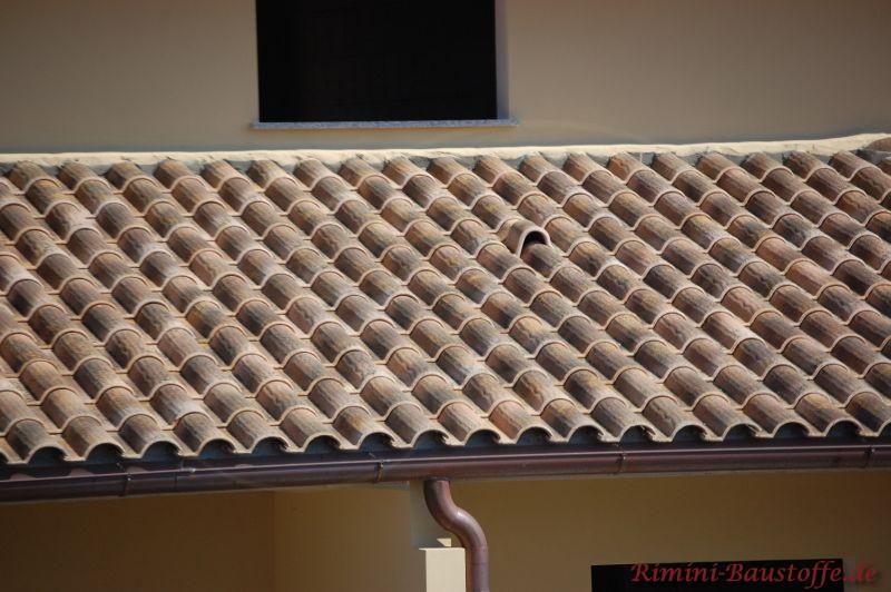 Dachüberstand im romanischem Stil. Die Dachpfannen sind rustikal und kleinformatig